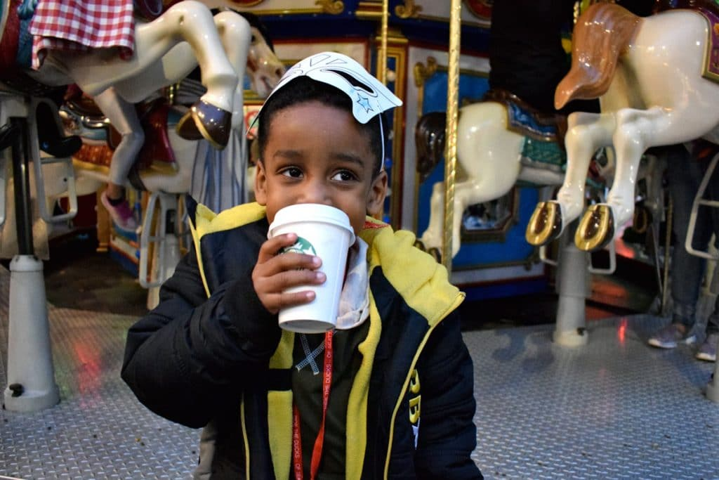 boy-sipping-cocoa-at-the-carousel